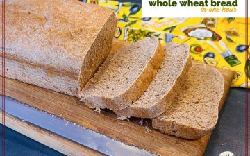 "loaf of whole wheat bread on a cutting board with a bread knife and text overlay ""Whole Wheat Bread in one hour"""