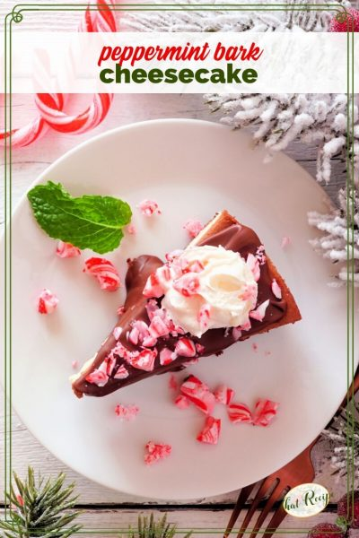 chocolate peppermint cheesecake on a plate with flocked greens and candy canes on table