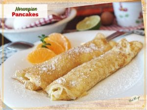 """rolled pancakes on a plate with orange slices and text overlay """" Norwegian Pancakes"""""""