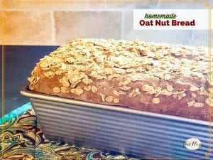 """loaf of oatmeal bread in the pan on a counter with text overlay """"homemade Oat Nut Bread"""""""