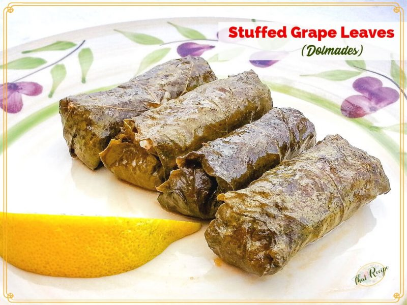 """4 dolmades on a plate with a slice of lemon and text overlay """"Stuffed grape leaves (dolmades)"""
