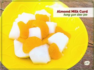 """bowl of white gelatin cubes and mandarin oranges with text overlay """"almond milk curd: hung yun dow foo"""""""