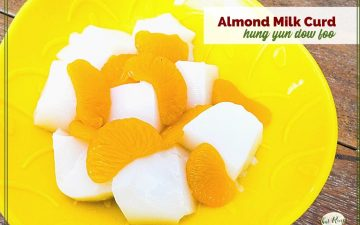 "bowl of white gelatin cubes and mandarin oranges with text overlay ""almond milk curd: hung yun dow foo"""