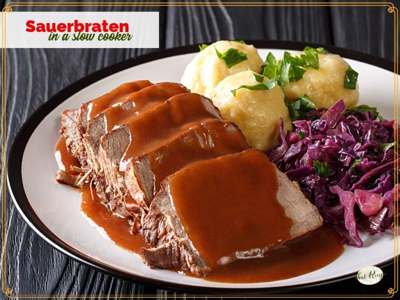 sliced sauerbraten on a plate with gravy, potatoes and red cabbage