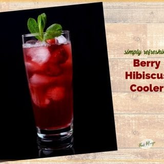 """glass of hibiscus tea with raspberries and text overlay """"Berry Hibiscus Cooler"""""""