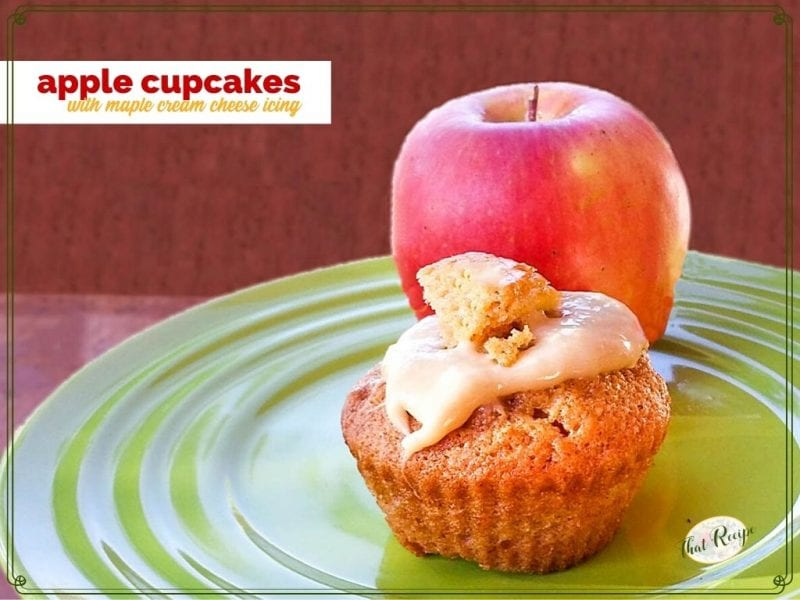 """Cupcake on a plate with an apple and text overlay """"Apple Cupcakes with Maple Cream Cheese Icing"""""""