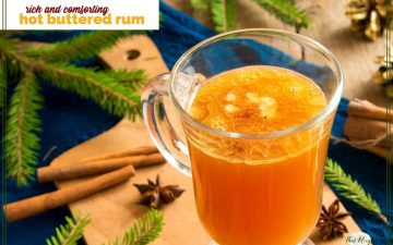 "clear glass mug of hot buttered rum with text overlay ""rich and comforting hot buttered rum"""