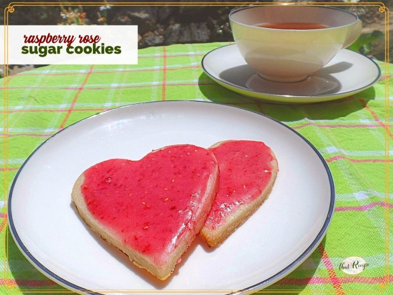 """two heart shaped cookies with pink frosting and a cup of tea on a table with text overlay """"Raspberry Rose Sugar Cookies"""""""