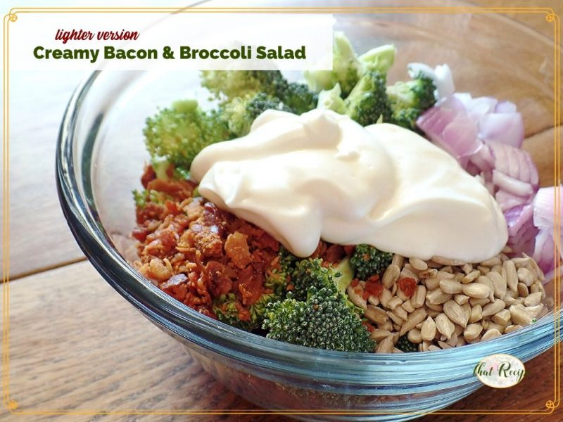 "bacon and broccoli salad ingredients in a bowl with text overlay ""lighter version creamy bacon and broccoli salad"""