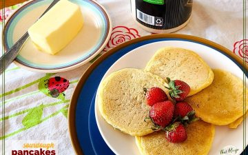 sourdough pancakes on a plate on a table with butter and syrup
