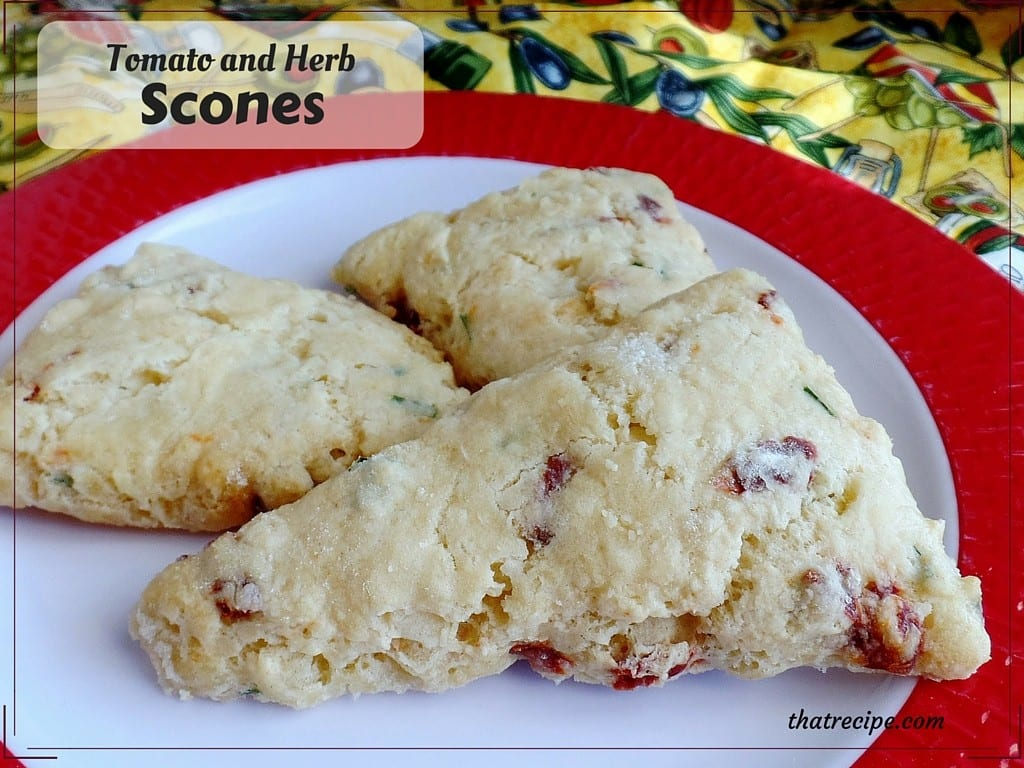 "scones on a plate with text overlay ""tomato and herb scones"""