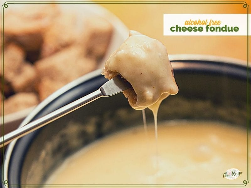 """piece of bread dipped in cheese fondue with text overlay """"alcohol free cheese fondue"""""""