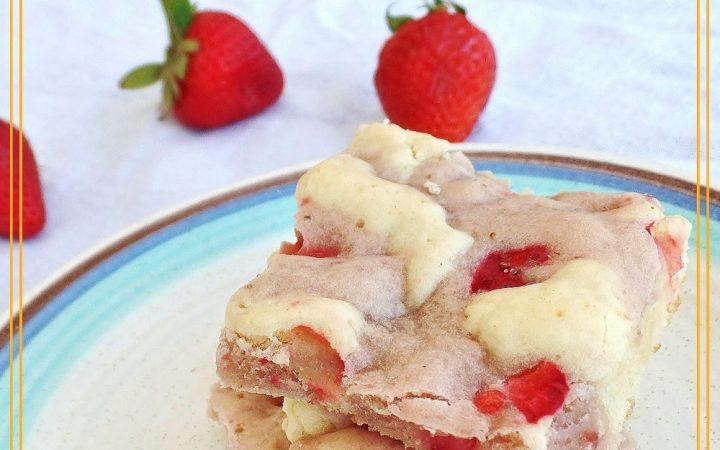 "cookie bars on a plate with fresh strawberries in the background with text overlay ""Fresh Strawberry Cream Cheese Swirl Bars"""