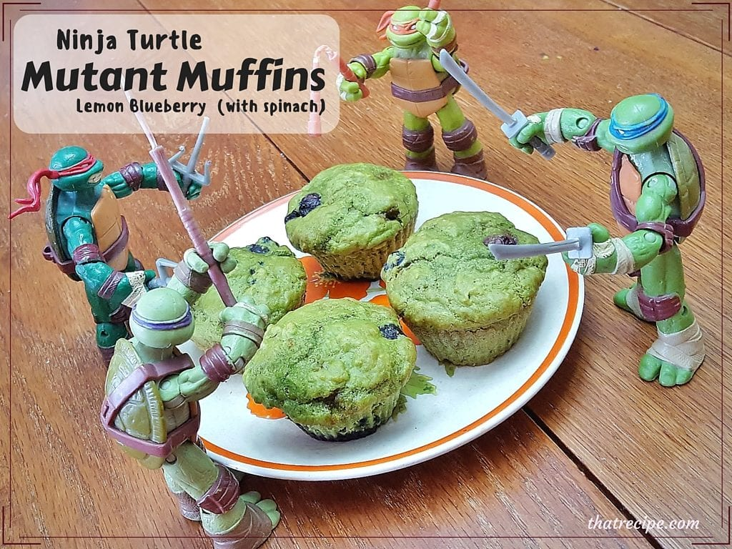 "plate of green blueberry muffins with TMNT action figures around it and text overlay ""Ninja Turtle Mutant Muffins Leon Blueberry (with spinach)"""