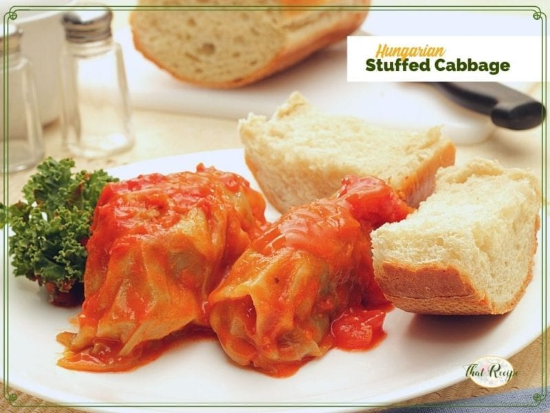 """cabbage rolls on a plate with bread and text overrlay """"Hungarian stuffed cabbage"""""""