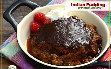 """pudding in a black dish with text overlay """"Indian Pudding cornmeal pudding"""""""