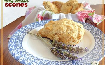 """scone on a plate with fresh lavender and bowl of more scones in background with text overlay """"honey lavender scones"""""""