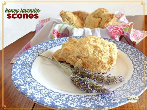 "scone on a plate with fresh lavender and bowl of more scones in background with text overlay ""honey lavender scones"""