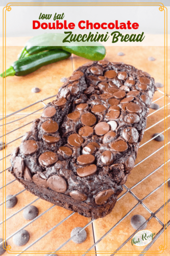 chocolate zucchini bread on a rack with fresh zucchini and chocolate chips