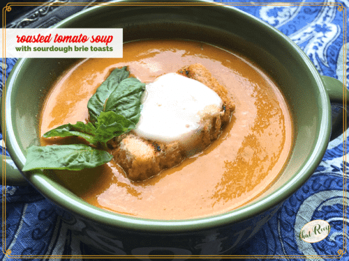 bowl of tomato soup with fresh basil and sourdough brie toast on top