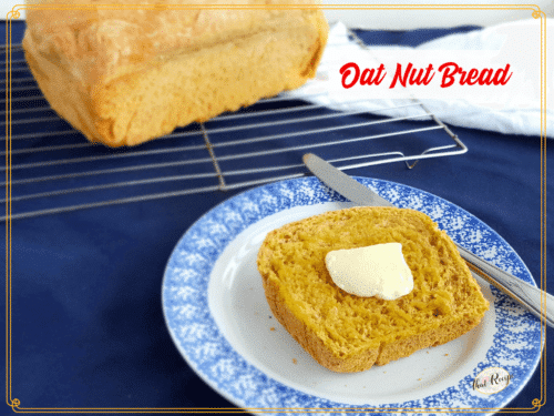 Slice of buttered Oat Nut Bread with whole loaf in the background