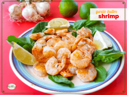 "stir fried butter and garlic shrimp with limes and raw garlic in the background with text overlay ""garlic butter shrimp"""