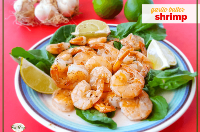 """stir fried butter and garlic shrimp with limes and raw garlic in the background with text overlay """"garlic butter shrimp"""""""