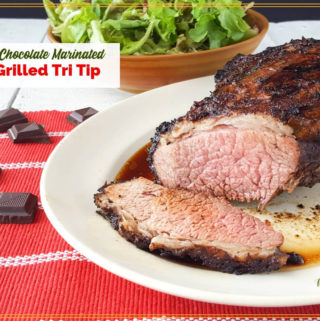 """tri tip roast on a plate with a salad and chocolate pieces and text overlay """"Spiced Chocolate Marinated Grilled Tri Tip"""""""