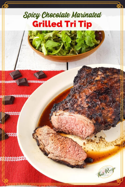 "tri tip roast on a plate with a salad and chocolate pieces and text overlay ""Spiced Chocolate Marinated Grilled Tri Tip"""