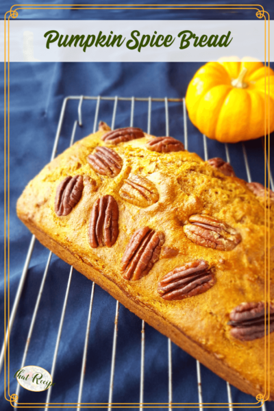 loaf of pumpkin spice bread on cooling rack with mini pumpkin
