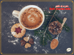 "top down view of mug of hot cocoa with cookies with text overlay ""Gifts in a Jar: Hot Cocoa Mix"""