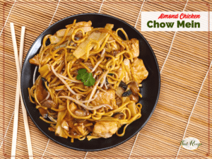 chow mein on a black plate with chopsticks on a bamboo mat with text overlay Almond Chicken chow mein