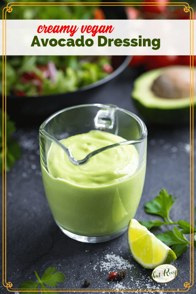 "avocado salad dressing in a glass jug on a table with salad and text overlay ""creamy vegan Avocado Salad Dressing"""