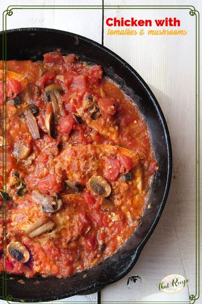 top down view of cast iron skillet with chicken tomatoes and mushrooms