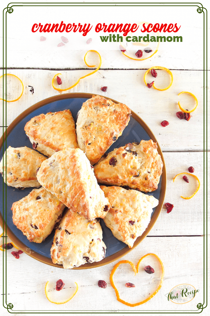 cranberry orange scones on a blue plate on a white table with orange peel and dried cranberries scattered about.