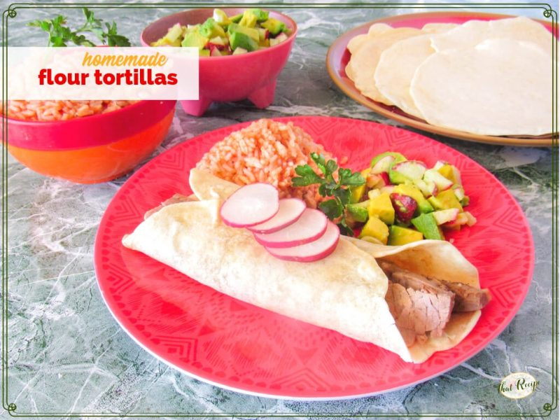 """steak burrito on a plate with Mexican rice, avocado salsa and flour tortillas in the background with text overlay """"homemade flour tortillas"""""""