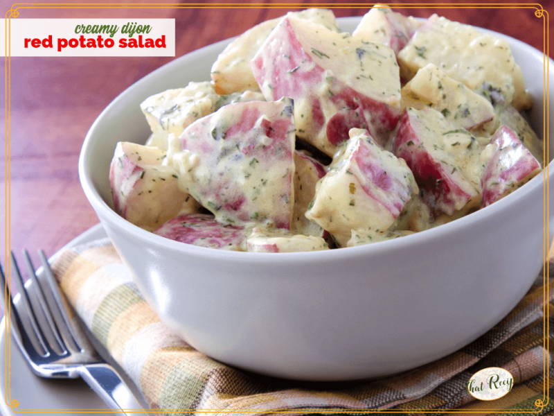 "bowl of red potato salad on a table with text overlay ""Creamy Dijon Potato Salad"""