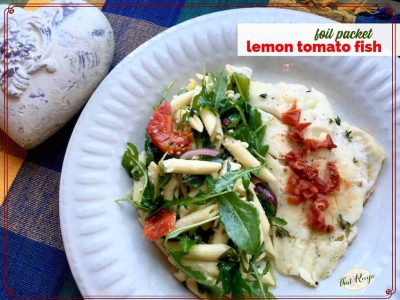 "top down view of fish and pasta salad on a plate with text overlay ""foil packet lemon tomato fish"""
