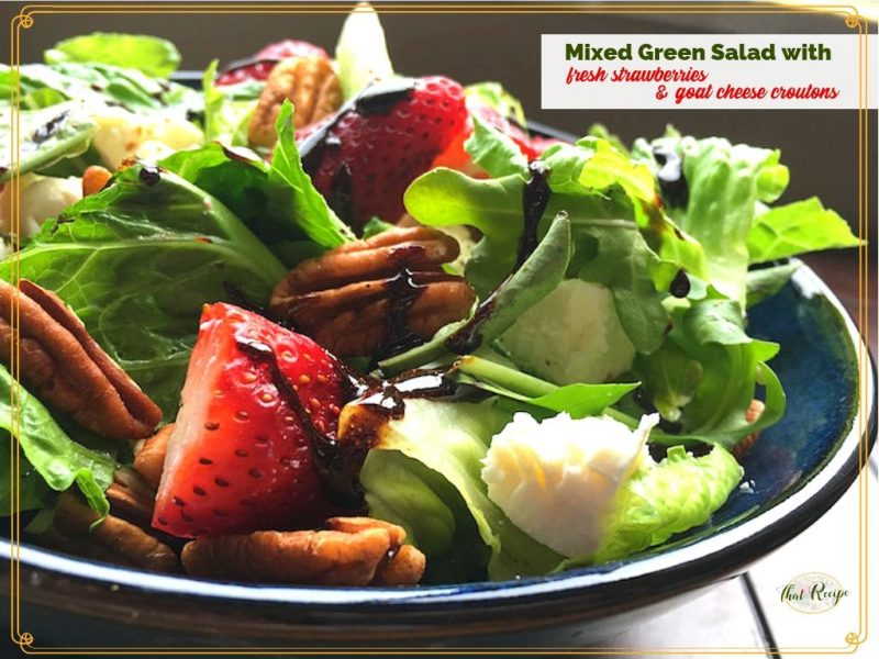 green salad with strawberries and goat cheese in a bowl