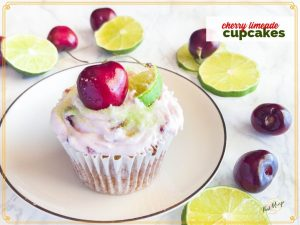 cherry limeade cupcake on a plate with fresh cherries and limes