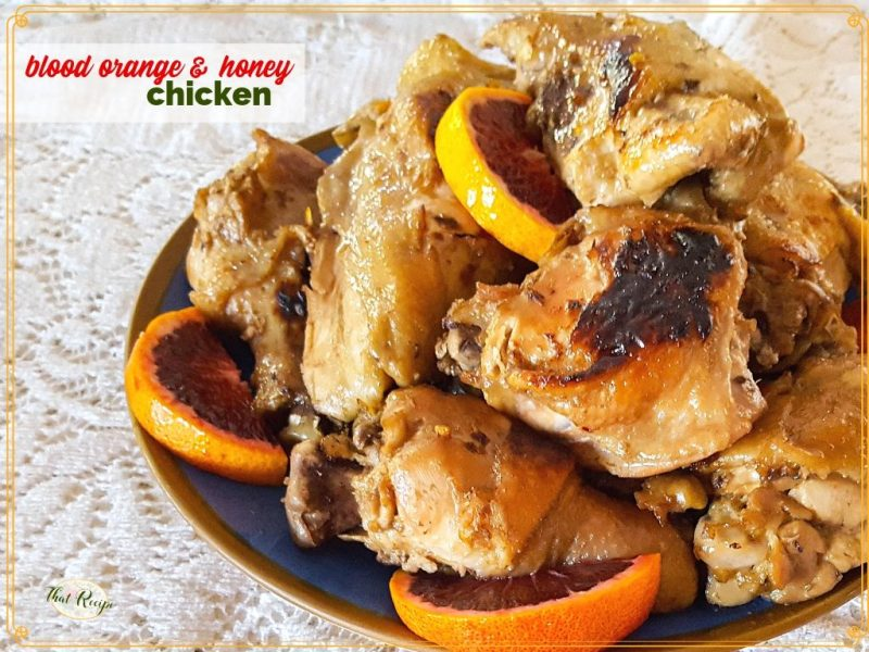 "plate of cooked chicken pieces with blood orange slices and text overlay ""Blood orange and honey chicken"""