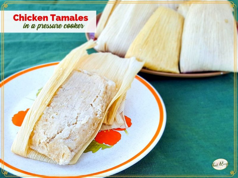 opened chicken tamale on a plate with plate of unopened tamales