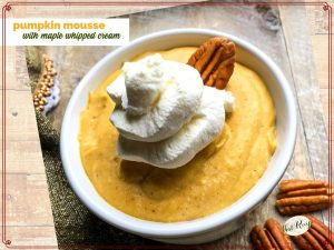 pumpkin mousse in a bowl with maple whipped cream and pecans