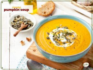 pumpkin soup topped with yogurt and pumpkin seeds