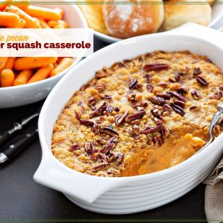 squash casserole on a table with carrots and rolls.