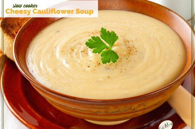 bowl of cheesy cauliflower soup in a brown bowl on a red charger plate