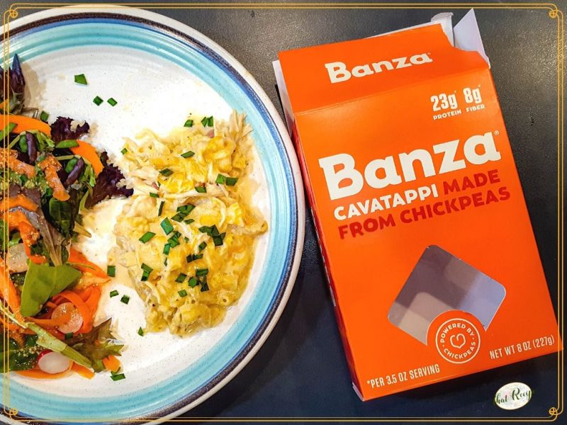 cheese pasta bake on a plate with a salad with a box of Banza pasta