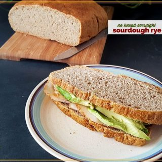 """turkey and avocado sandwich on rye bread with loaf of ry bread in the background and text overlay """"sourdough rye bread"""""""