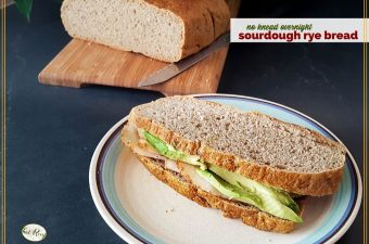 "turkey and avocado sandwich on rye bread with loaf of ry bread in the background and text overlay ""sourdough rye bread"""