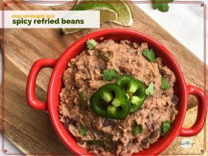 bowl of refried beans on a chopping block with limes